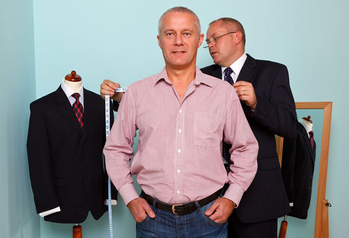 A tailor measuring the shoulder width of a man for the fitting of a new bespoke suit
